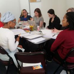Cast members for <em>The Swallowing Dark</em> along with director Claire Moyer sit at their first table read rehearsal.