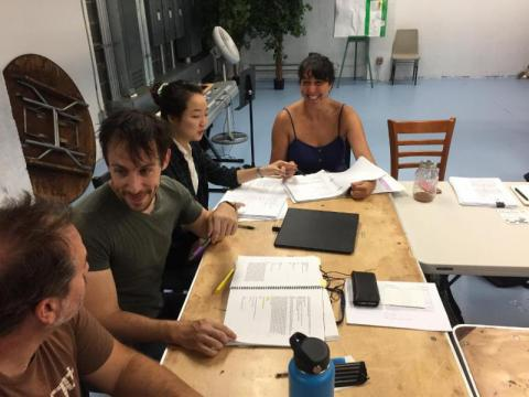 The cast of Monster in the Hall sit at a table read